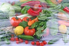 Variedad de frutas y verduras org?nicas crudas frescas en los envases marrones claros que se sientan en fondo de madera azul bril foto de archivo libre de regalías