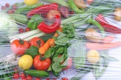 Variedad de frutas y verduras org?nicas crudas frescas en los envases marrones claros que se sientan en fondo de madera azul bril imagenes de archivo