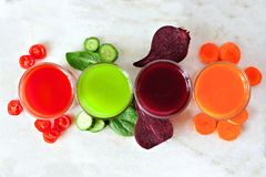 Variedad de jugo con las verduras dispersadas, sobre la opinión sobre el mármol Imagen de archivo libre de regalías