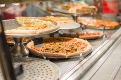 Variedad de pizzas deliciosas bajo ventana de las compras Imagen de archivo