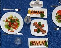 Variedad de platos deliciosos en las placas en mantel azul en el restaurante Imágenes de archivo libres de regalías