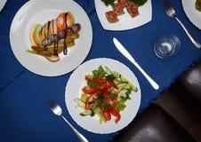 Variedad de platos deliciosos en las placas en mantel azul en el restaurante Imagen de archivo libre de regalías