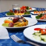 Variedad de platos deliciosos en las placas en mantel azul en el restaurante Fotografía de archivo libre de regalías
