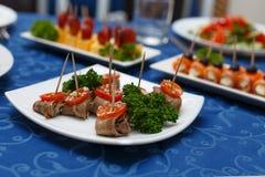 Variedad de platos deliciosos en las placas en mantel azul en el restaurante Fotografía de archivo
