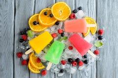 Variedad de polos sanos del hielo con las frutas y las bayas en el hielo imagenes de archivo