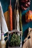 Variedad de salchichas del charcuterie que cuelgan en la guita en los ganchos, bardo de madera del corte, hierbas, toalla de lino Imágenes de archivo libres de regalías
