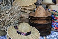 Variedad de sombreros de paja en la tabla en el mercado al aire libre de la isla Fotos de archivo libres de regalías