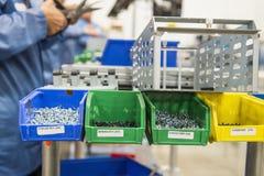 Variedad de tornillos en bandeja con los ingenieros que trabajan en la industria de electrónica Fotografía de archivo