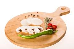 Variedad de verduras en el tablero de madera - pimientas, romero, tomates, cebolla y seta imagenes de archivo