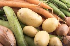 Variedad de verduras incluyendo zanahorias, habas, cebollas y patatas Imagenes de archivo