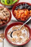 Variedad sana del desayuno de comida en la tabla de cocina de madera blanca El cereal forma escamas con leche, frutas secadas y n Imágenes de archivo libres de regalías