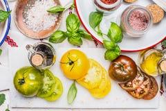 Variedade colorida cortada dos tomates na placa de corte de mármore na mesa de cozinha clara com os ingredientes em umas bacias e Foto de Stock Royalty Free