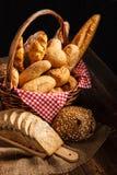Variedade da padaria na tabela de madeira no fundo escuro Ainda vida da variedade de pão com luz natural da manhã Imagens de Stock
