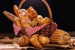 Variedade da padaria na tabela de madeira no fundo escuro Ainda vida da variedade de pão com luz natural da manhã Foto de Stock Royalty Free