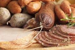 Variedade da salsicha e da carne na placa de corte Imagem de Stock