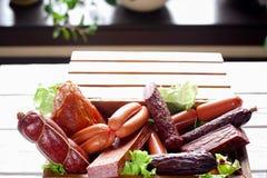 Variedade da salsicha no close-up da caixa de madeira Imagens de Stock