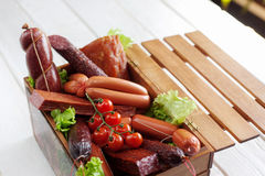 Variedade da salsicha no fundo do branco da caixa de madeira Imagem de Stock