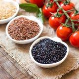Variedade de arroz em umas bacias e em uns tomates Foto de Stock Royalty Free