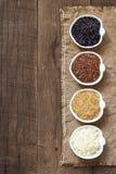 Variedade de arroz em umas bacias na tabela de madeira Foto de Stock Royalty Free