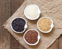 Variedade de arroz em umas bacias na tabela de madeira Fotos de Stock Royalty Free