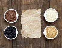 Variedade de arroz em umas bacias na tabela de madeira e no papel velho Foto de Stock Royalty Free