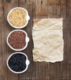 Variedade de arroz em umas bacias na tabela de madeira e no papel velho Imagem de Stock