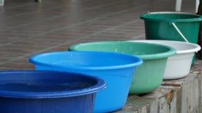 Variedade de bacias plásticas com água que está na rua filme