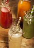 Variedade de batidos das frutas e legumes nas garrafas de vidro com palhas Fotos de Stock Royalty Free