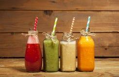 Variedade de batidos das frutas e legumes nas garrafas de vidro com palhas Fotografia de Stock