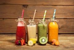 Variedade de batidos das frutas e legumes nas garrafas de vidro com palhas Imagens de Stock