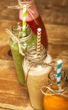 Variedade de batidos das frutas e legumes nas garrafas de vidro com palhas Imagem de Stock Royalty Free