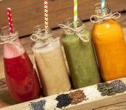 Variedade de batidos das frutas e legumes nas garrafas de vidro e nas sementes Fotografia de Stock
