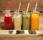 Variedade de batidos das frutas e legumes nas garrafas de vidro e nas sementes Fotos de Stock Royalty Free