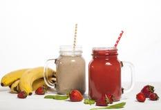 Variedade de batidos das frutas e legumes nas garrafas de vidro com palhas Foto de Stock Royalty Free