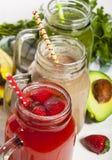 Variedade de batidos das frutas e legumes nos frascos de vidro com palhas Foto de Stock