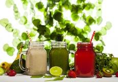 Variedade de batidos das frutas e legumes nos frascos de vidro com palhas Foto de Stock Royalty Free
