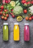 A variedade de batidos ou de bebidas coloridas dos sucos bebe em umas garrafas com ingredientes frescos: frutos, bagas e vegetais Imagem de Stock Royalty Free