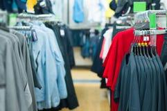 Variedade de camisas, de t-shirt e de revestimentos em carrinhos fotografia de stock royalty free