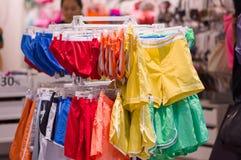 Variedade de camisas e de calças no carrinho na alameda imagens de stock