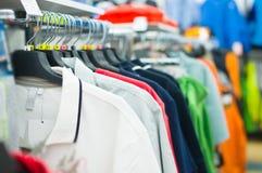 Variedade de camisas e de t-shirt em carrinhos na loja Foto de Stock Royalty Free