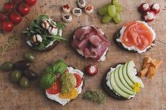 Variedade de canape com salmões, prosciutto, abacate, mussarela, tomate, pesto, azeitonas, queijo creme Mistura de petiscos e de  Foto de Stock Royalty Free