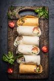 Variedade de envoltórios saborosos do vegetariano na placa de corte rústica no fundo escuro, vista superior Almoço saudável Fotografia de Stock