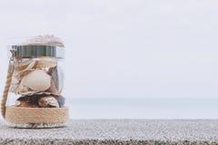 Variedade de escudos do mar no frasco de vidro e de seascape no fundo com espa?o da c?pia Conceito do feriado imagem de stock