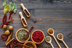 Variedade de especiarias e de ervas secas em umas bacias no modelo de madeira da opinião superior do fundo da mesa de cozinha Imagens de Stock