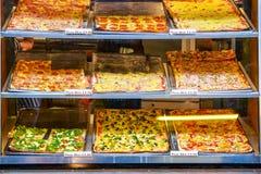 Variedade de fatias da pizza na exposição para o takeaway em Camden Market em Londres fotografia de stock royalty free