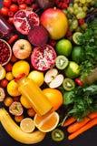 Variedade de frutas e legumes diferentes em cores do arco-íris com os batidos em umas garrafas foto de stock