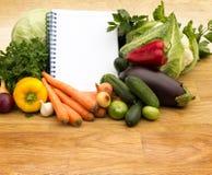 A variedade de legumes frescos e a receita vazia registram Fotografia de Stock Royalty Free