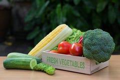 Variedade de legumes frescos na caixa de madeira na tabela de madeira Fotografia de Stock Royalty Free