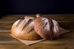 Variedade de Loafs Rye cozido fresco e de pão inteiro da grão na variedade escura da foto do fundo de madeira da textura de pão Imagens de Stock