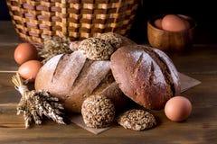 Variedade de Loafs Rye cozido fresco e de pão inteiro da grão na variedade escura da foto do fundo de madeira da textura de pão Foto de Stock Royalty Free